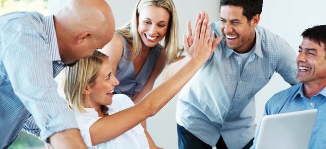 Excited businesspeople giving each other high five for successfu