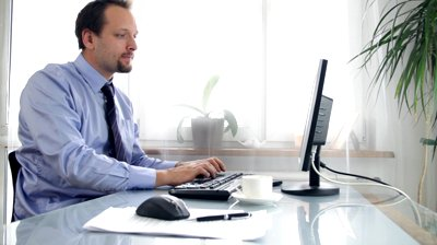 stock-footage-businessman-working-on-laptop-and-smiling-to-the-camera
